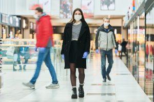 Menschen mit Gesichtsmasken gehen durch Flughafen