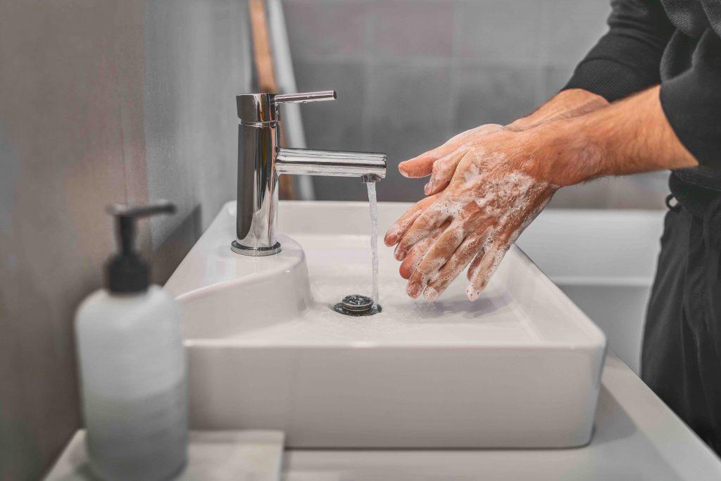 Person wascht Hände im Waschbecken