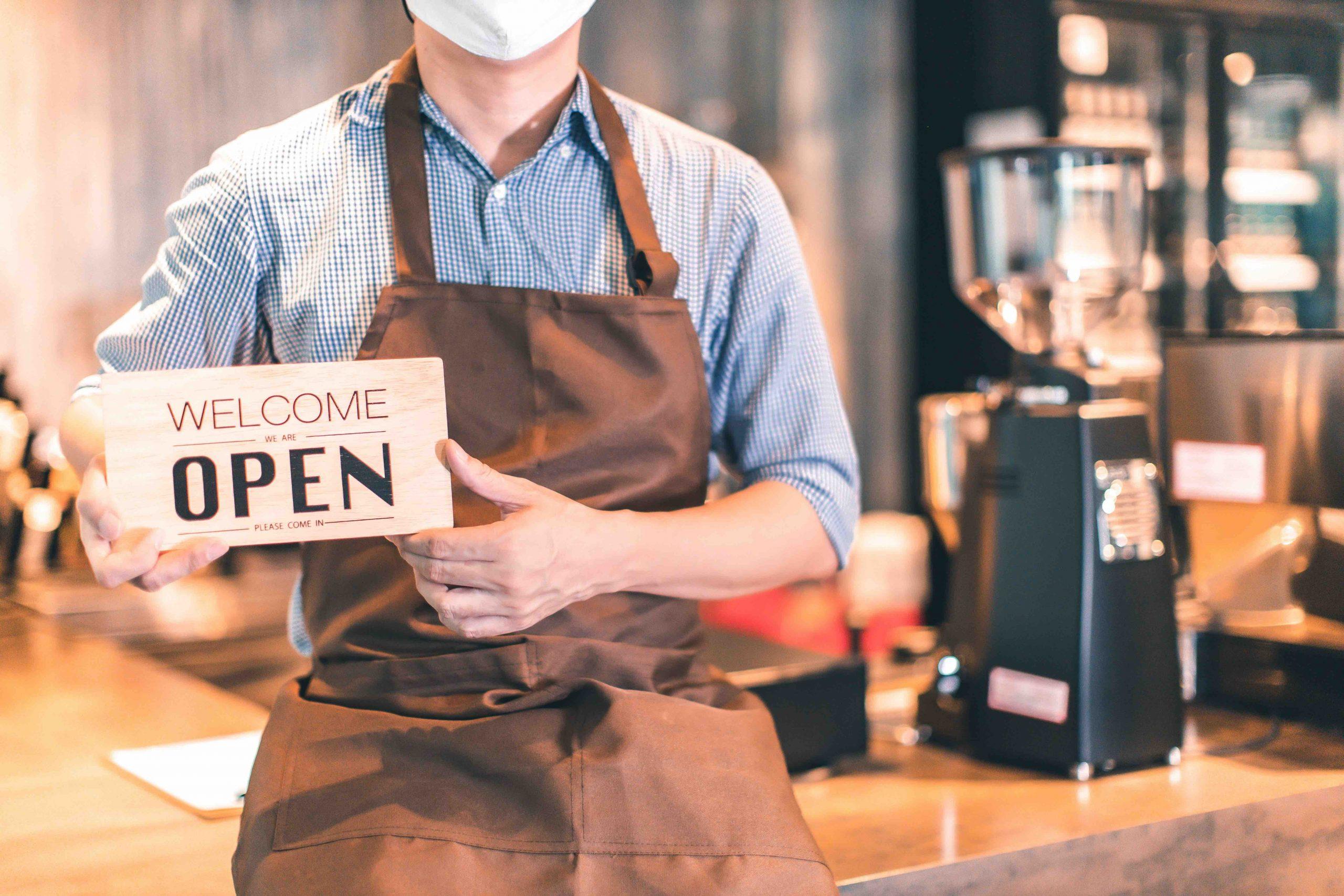 Kaffee Besitzer mit Schild in der Hand